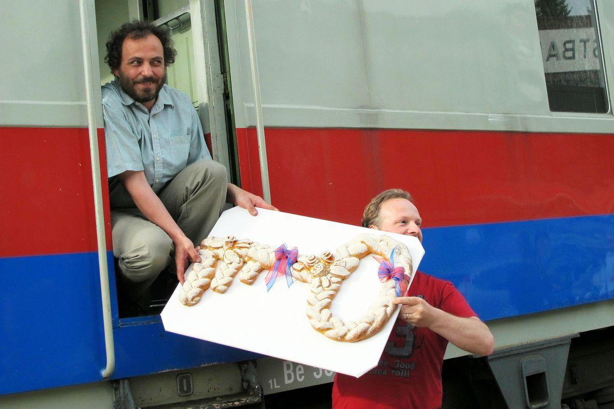 Johann Gröbli nimmt in der Führerstandstüre kniend den symbolischen Schlüssel aus Brot-Teig des Triebwagens BDe 3/4 Nr. 43 der ehemaligen BT, auch bekannt als TINO, entgegen. Herisau 29.04.2011 | Bild: H.U. Kneuss