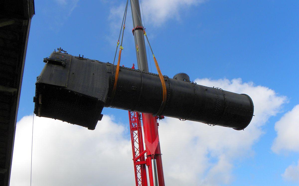 Der Kessel der C 5/6 2958 schwebt hoch am blauen Himmel an zwei Seilen am Haken eines riesigen Pneukranes 29.05.2010 | Bild: M. Simmons