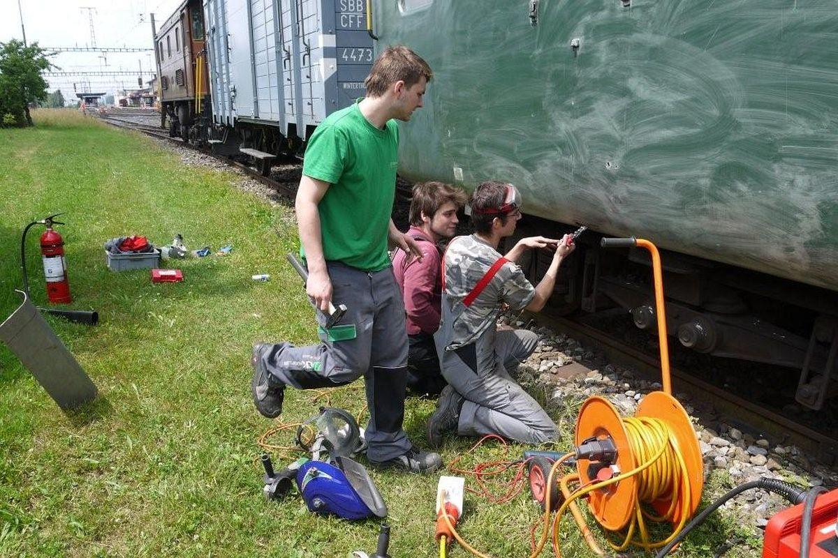 3 Lehrlinge kümmern sich um eine Schadstelle an der unteren Kante eines Leichtstahler-Wagenkastens 26. Juni 2013   Bild: Josef Angehrn