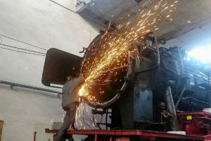 Ein Mitarbeiter der Eisenbahn-Werkstätten Krefeld bearbeitet mit einem Winkelschleifer die Dichtfläche der Rauchkammertür der 23 058, die Funken sprühen nur so im Rechteckschuppen des ehemaligen Bw Heilbronn 01. Februar 2019 | Bild: EV-Gruppe 23058 /ZVG