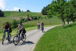 Vier Elektrovelo-Fahrerinnen und Fahrer auf Nebenstrassen sind in der hügligen Landschaft des Emmentals unterwegs 21. Mai 2011 | Bild: H.U. Kneuss