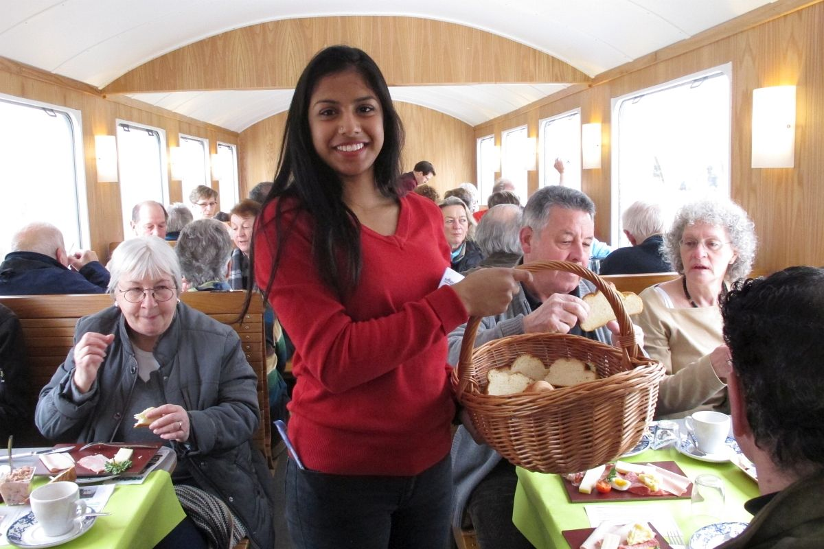 Soniya geht mit einem Korb frisch geschnittener Zopfscheiben durch das Abteil in dem ausgiebig gebruncht wird, 15. Februar 2015   Bild: H.U. Kneuss