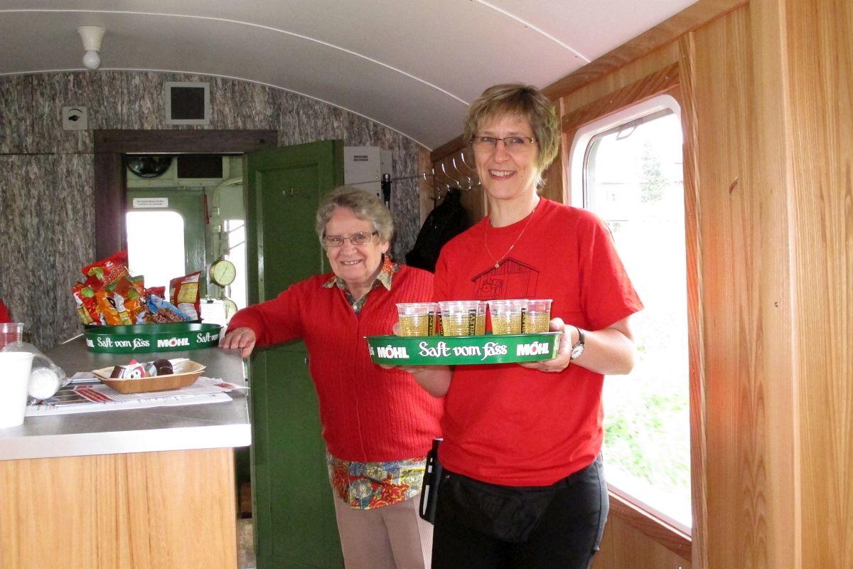 Charmanter Service: Hildi & Sonja verteilen Shorley im neu renoviertem Apfelsaft-Express während der Pendelfahrten der Bischofszeller Rosenwoche am 23. Juni 2013