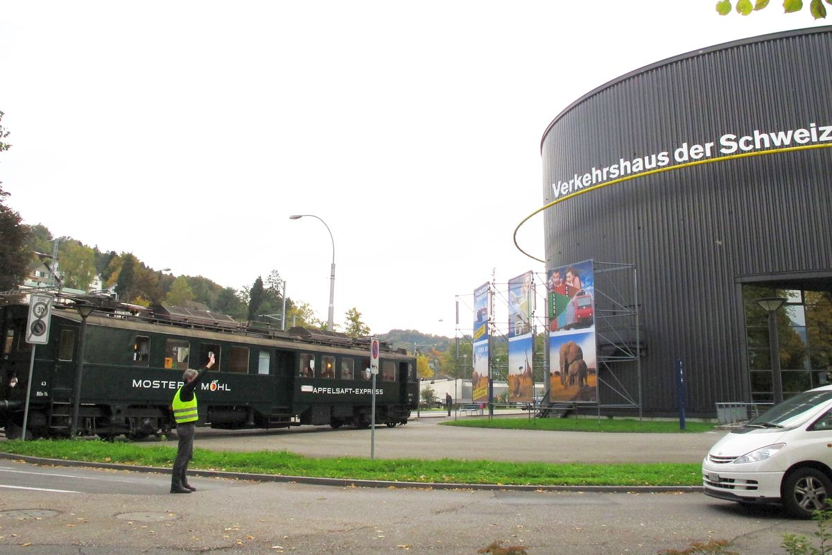 Ein Auto muss warten während unser Apfelsaft-Express ins Gelände des Verkehrshaus der Schweiz einfährt am 20. Oktober 2013 | Bild: H.U. Kneuss
