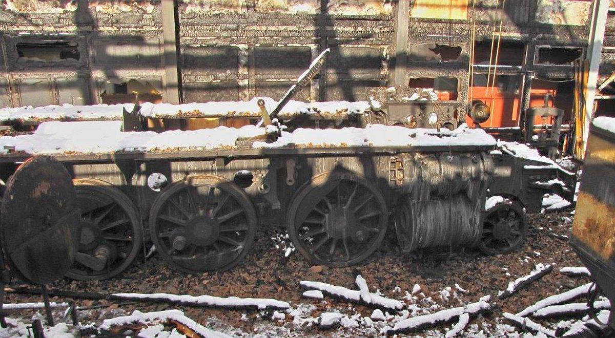 Nach dem Brand in der BDB-Werkstätte in Interlaken ist der Rahmen der C5/6 2969 mit Schnee und Bruchstücken von Dachziegeln bedeckt, die Räder rostig vom Löschwasser, 22.11.2013   Bild: Riccardo Keller