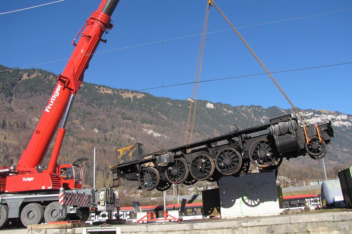 Der durch den Werkstatt-Brand beschädigte Rahmen unserer C 5/6 2969 wird vor der Bergkulisse Interlakens mit einem Pneukran angehoben um auf einen Strassentieflader abgesetzt zu werden, 17.12.2013 | Bild: Riccardo Keller