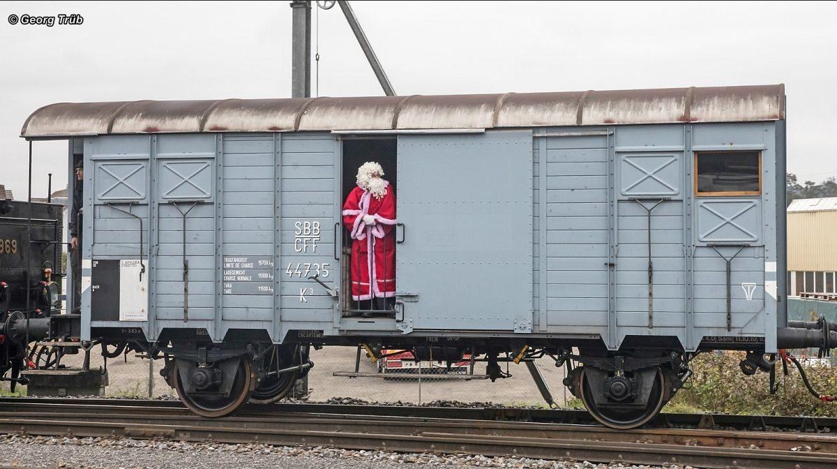 Der Chlaus schaut entlang es Extrazuges zum Tor des gedeckten Güterwagens Typ K3 Nr. 44735 hinaus. Wann geht's endlich weiter? 01. Dezember 2019 | Bild: Georg Trüb