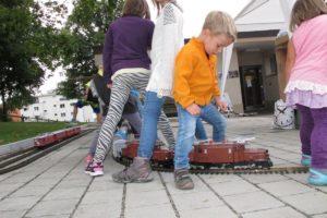 Kinder lassen die Gartenbahn-Züge zwischen ihren Beinchen durchfahren, welche vor unserem Stand am Dorffest Sulgen ihre Runden drehen. Der Erwachsene erfreut sich lieber am langen Güterzug mit zwei RhB-Krokodilen von LGB. 05. September 2015 | Bild: H.U. Kneuss