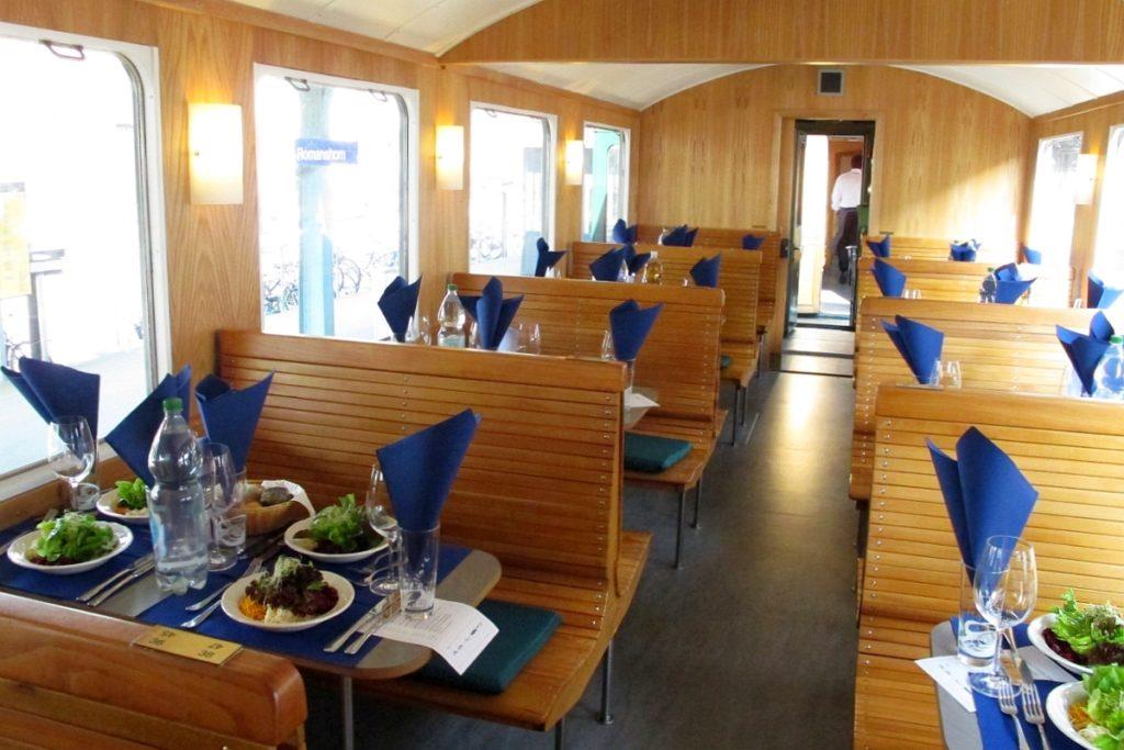 """Die anmächeligen Salatteller sind aufgetischt auf den schön gedeckte Tischen unseres rollenden Restaurants """"Apfels-Express"""". 10. März 2016 Bild: H.U. Kneuss"""