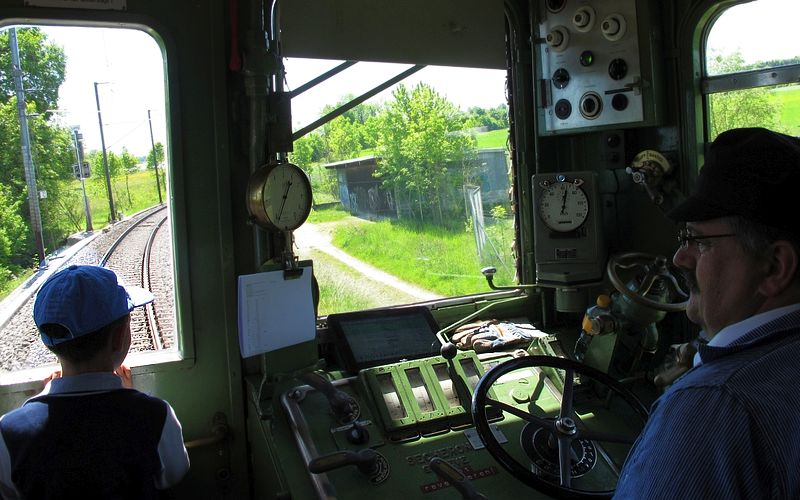 Fasziniert schaut der Junge aus dem schmalen Führerstandsfenster des Apfelsaft-Express auf die davorliegende Strecke, der Lokführer schaut derweil auf den paprierenen Dienstfahrplan.