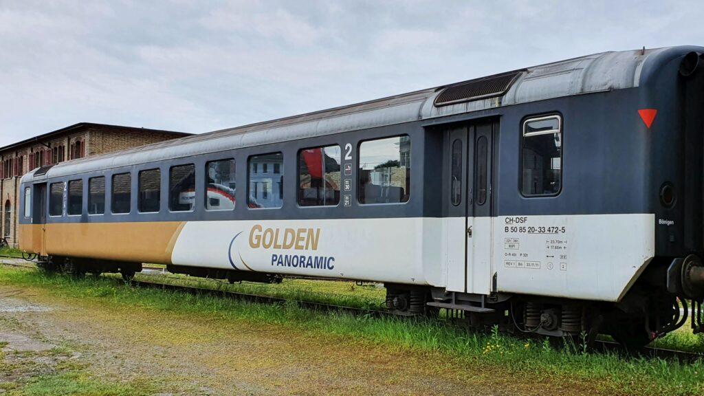 Personenwagen Typ EW I B 50 85 20-33 472-5. Das Fensterband ist in dunklem blau gehalten, der untere Teil der Wagens ist je hälftig weiss / goldig, mit dem Logo des Golden Panoramic im weissen Teil. Es ist ein Einheitswagen 1, 2. Klasse ehemalig BLS, ehemalig DSF. Nummer B 50 85 20-33 472-5. Aufgenommen in Romanshorn auf einem Abstellgleis vor dem Locorama am 05. Juni 2021. Bild: H.U. Kneuss